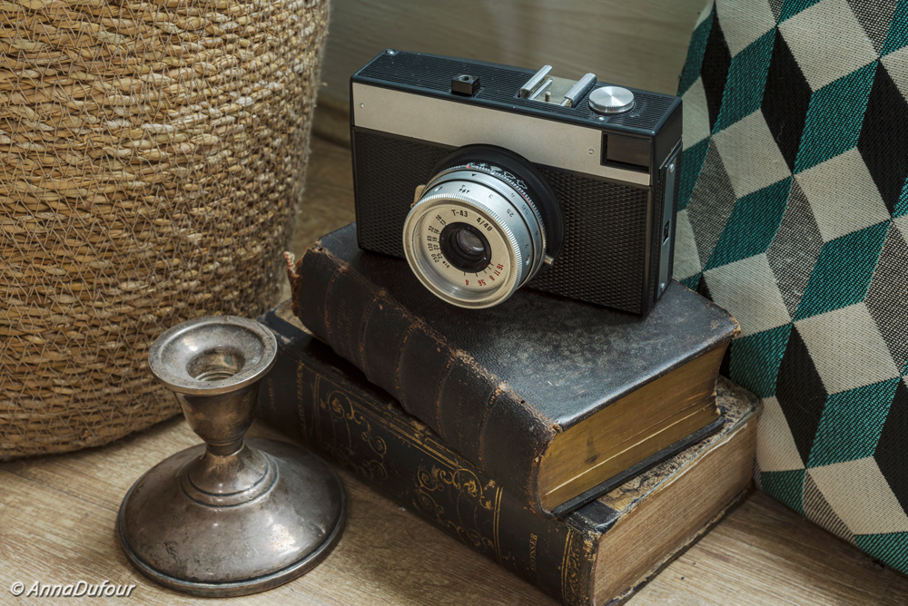 Old-photo-camera-placed-on-top-of-the-old-books-surrounded-by-silver-candlestick-and-blue-aqua-cusson-anna-dufour