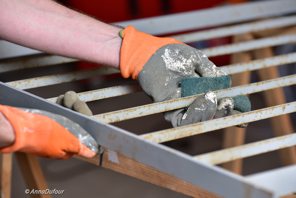 worker-cleaning-metal-grid-anna-dufour